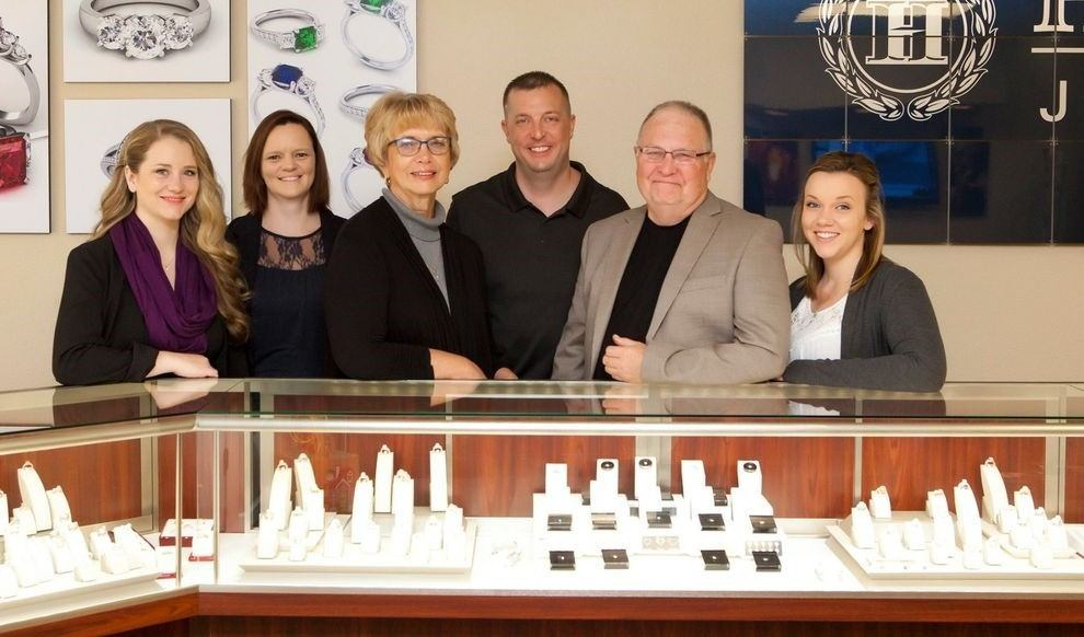 Photograph of Hustedt Jewelers Staff in front of Glass Display Case